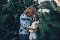 Couple Kissing Next To Pine Tree