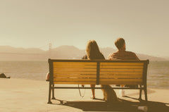 Couple Sitting On Bench Looking At Golden Gate Bridge