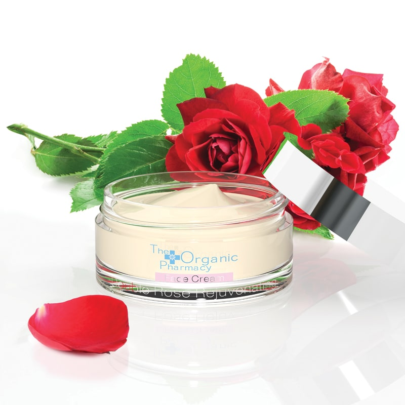 The Organic Pharmacy Double Rose Rejuvenating Face Cream (50 ml) lifestyle shot with red roses in the background and lid off jar