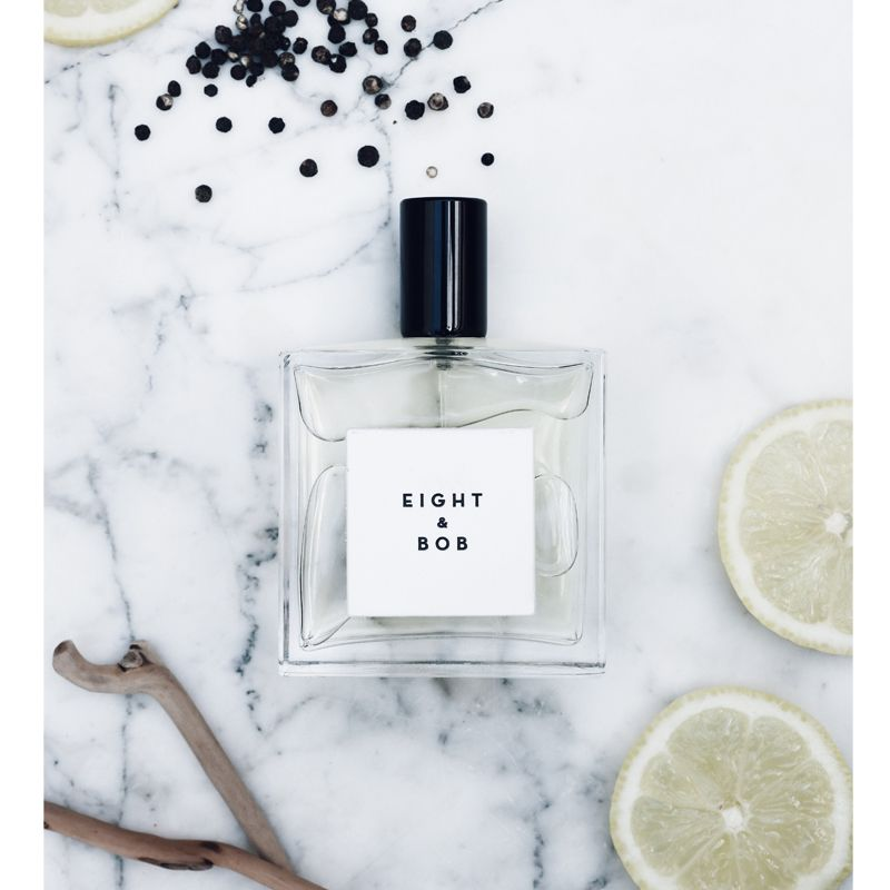 Beauty shot top view of Eight & Bob Original Eau de Parfum (100 ml) on marble table with slices of lemon and peppercorns