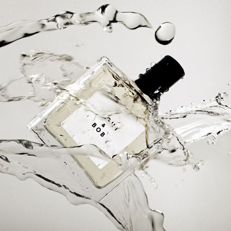 Beauty shot of Eight & Bob Original Eau de Parfum (100 ml) bottle enveloped with splash of eau de parfum
