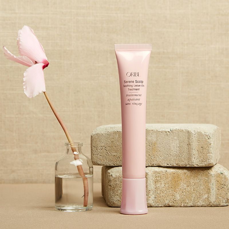 Oribe Serene Scalp Soothing Leave-On Treatment standing by bricks