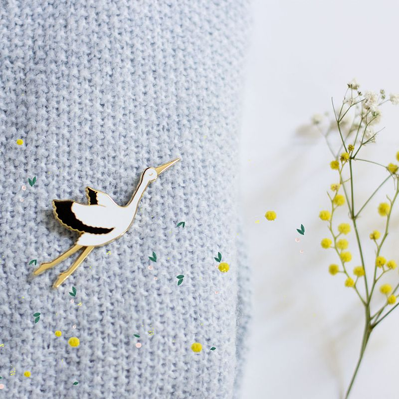 My Lovely Thing Jolie Bird Brooch (1 pc) beauty shot of pin on knit sweater and yellow flowers in the background