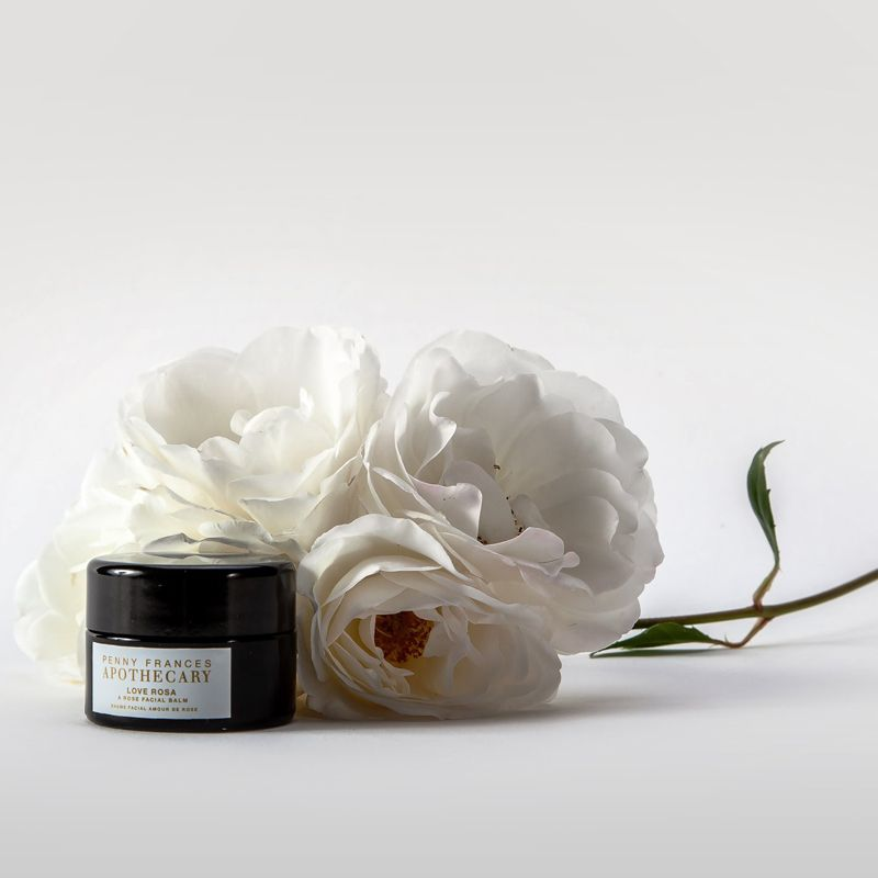 Penny Frances Apothecary Love Rosa A Rose Facial Balm Beauty shot with roses