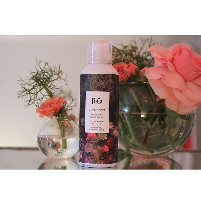 R+Co Centerpiece All-In-One Elixir Spray next to flowers