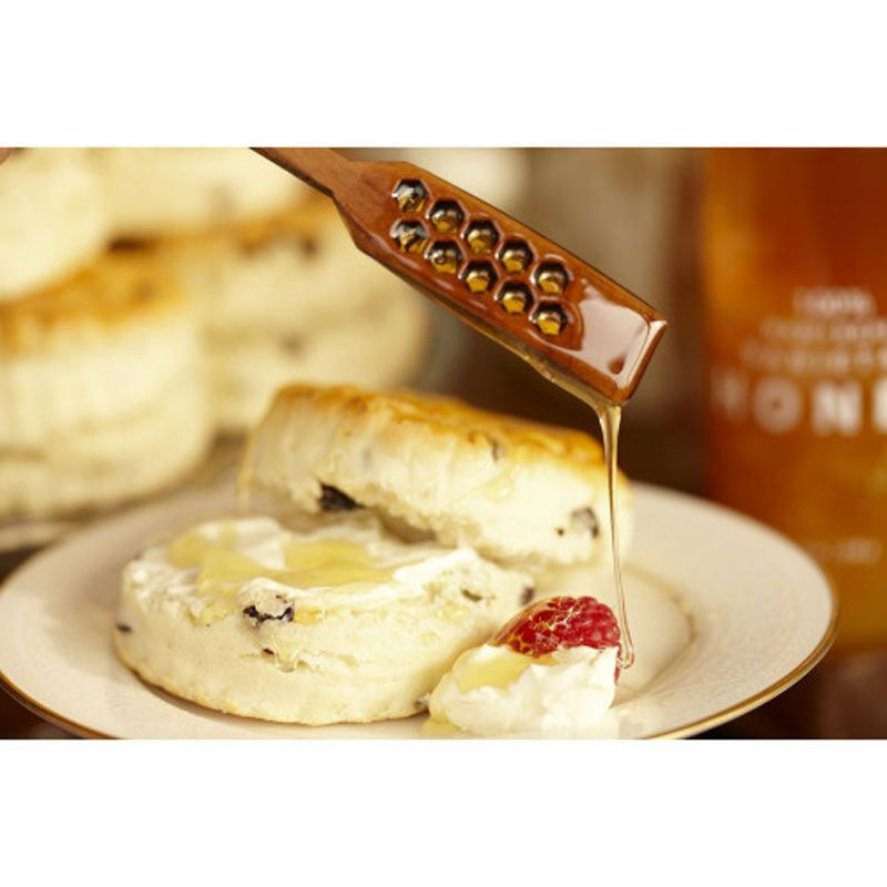 Bee Raw Cherry Wood Honey Stick shown dripping honey over biscuits