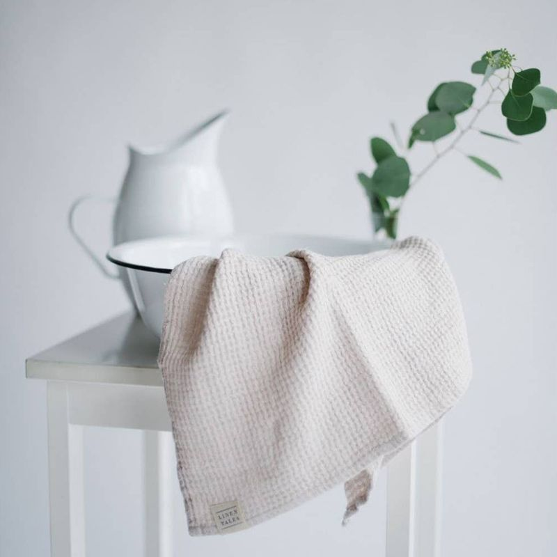 Linen Tales Waffle Hand Towel - Beige shown on table with pitcher and bowl