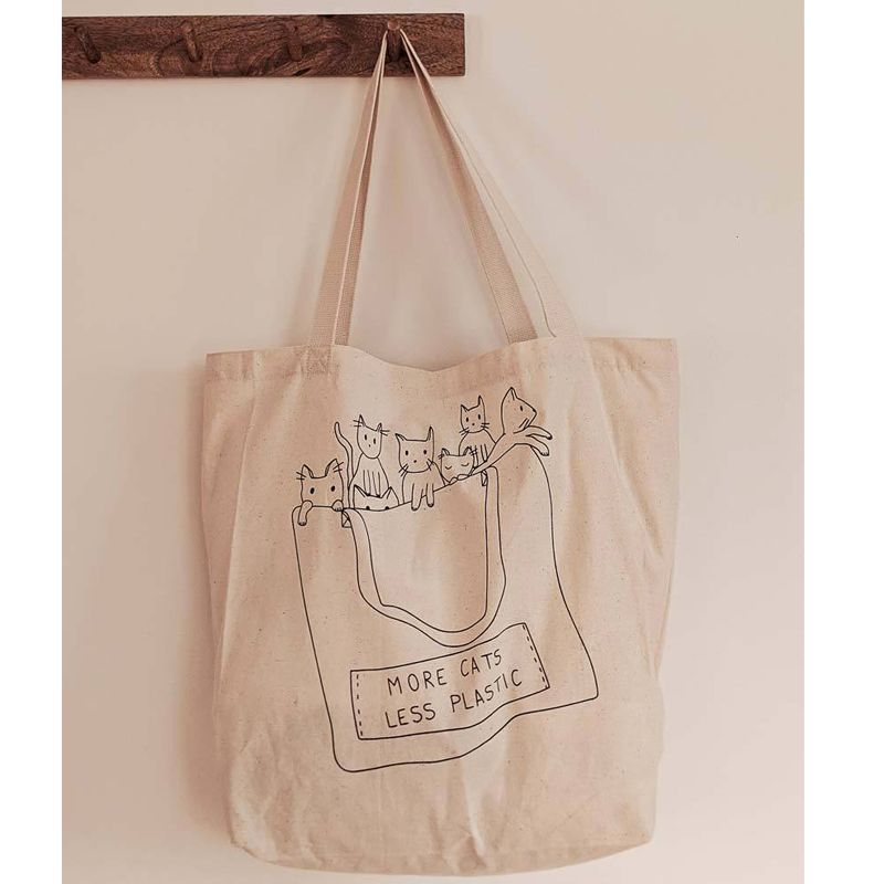 Mimi & August More Cats Less Plastic Printed Cotton Tote Bag hanging on peg