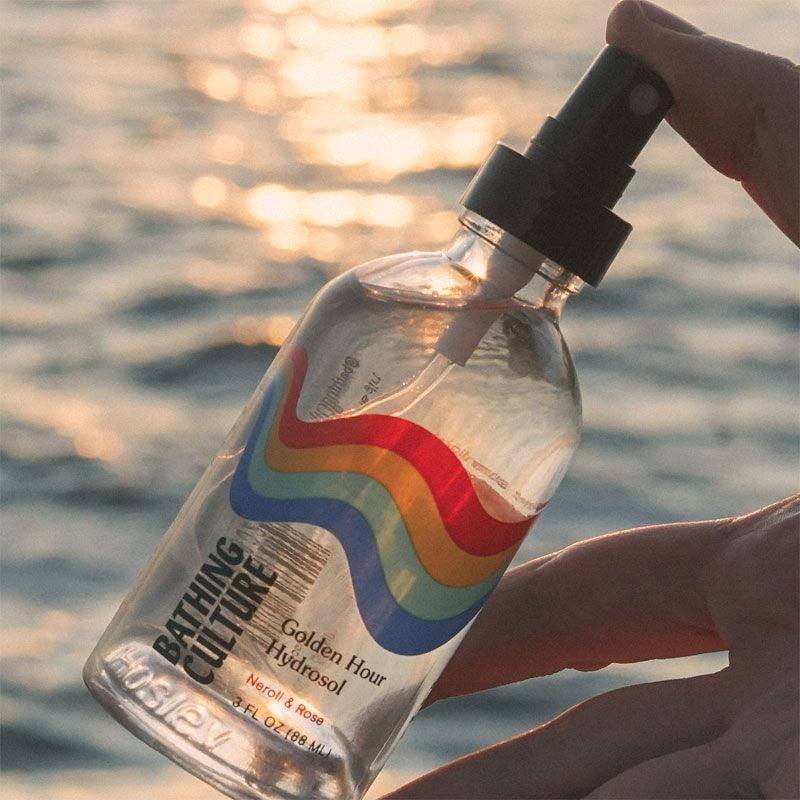 Bathing Culture Golden Hour Hydrosol in a hand in front of ocean
