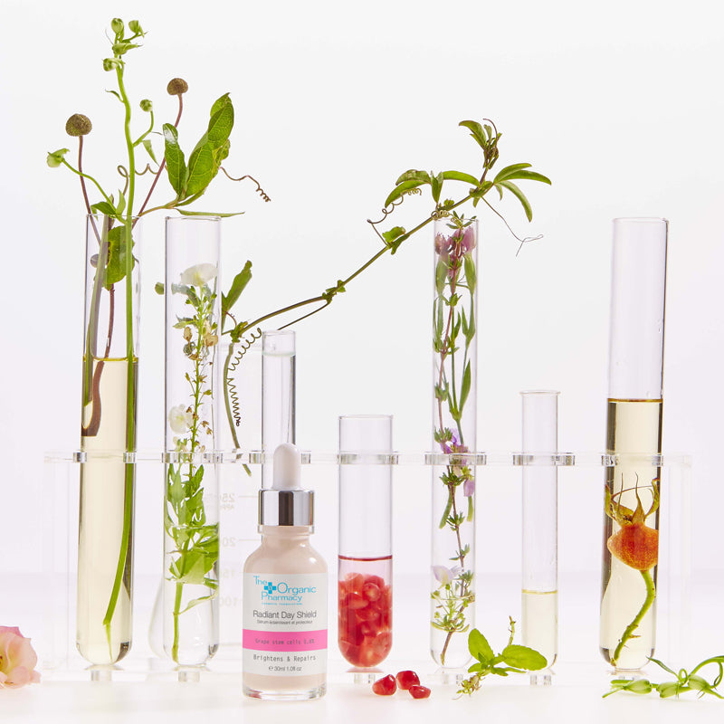 Beauty shot of Radiant Day Shield with test tubes filled with botanicals and oils in the background