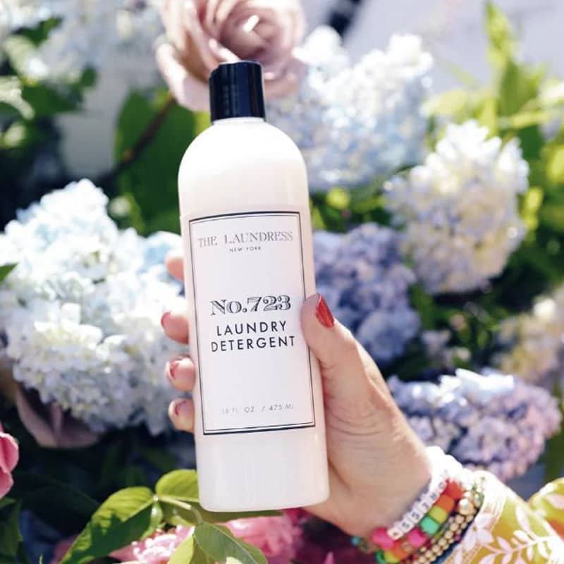 The Laundress No. 723 Laundry Detergent 16 oz in a hand with flowers in the background