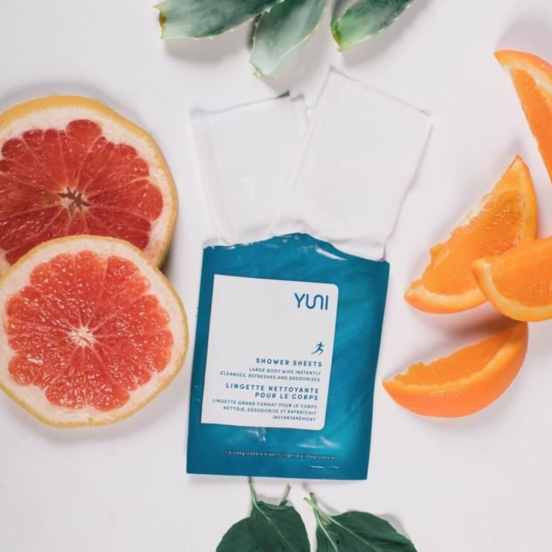 Yuni Beauty Neem Peppermint & Citrus Shower Sheets showing packet open and sheet coming out with citrus fruits