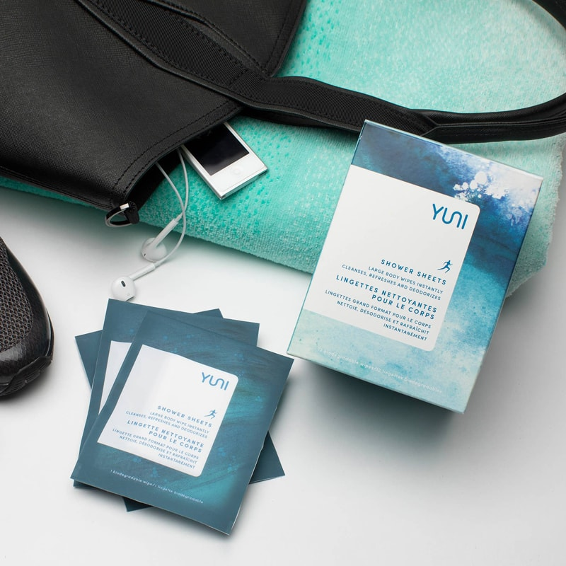 Yuni Beauty Neem Peppermint & Citrus Shower Sheets lifestyle shot showing shower sheet packets with purse