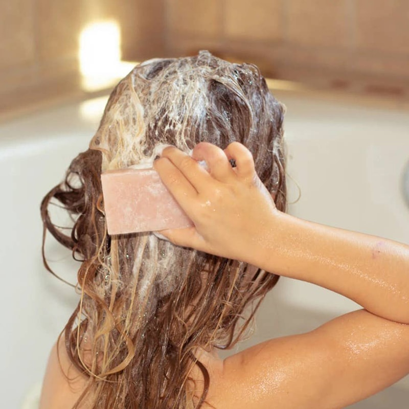 Moon Valley Organics Pink Geranium Shampoo Bar - shows model using the shampoo bar on hair