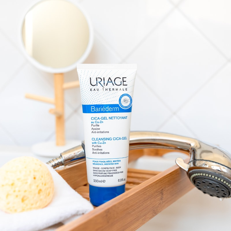 Lifestyle shot of Uriage Bariederm Cleansing Cica-Gel (6.8 oz) on wooden tray with vanity mirror, sponge and shower head in the background