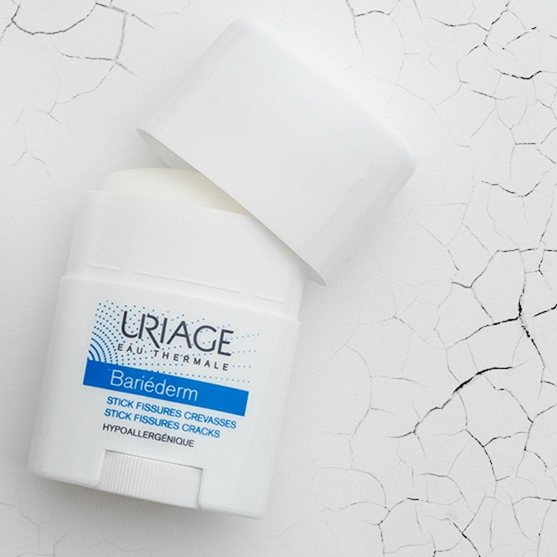 Lifestyle shot of Uriage Bariederm Stick Fissures Cracks Stick (0.77 oz) shown top view with cap off and cracked texture in the background