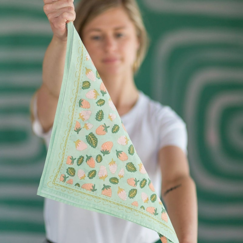 Hemlock Suzette Premium Cotton Handmade Bandana in model's hands in a triangle