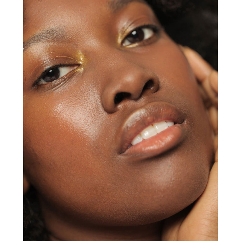 NOTO Botanics Gold Glow Stick on model's face - used to highlight lips, cheeks and inside eyes.