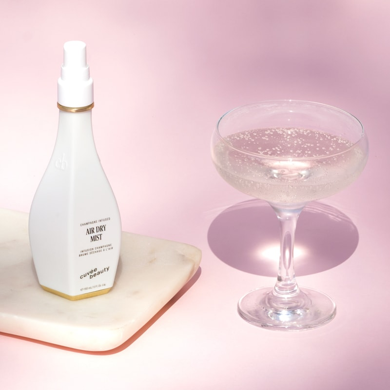 Cuvee Beauty Air Dry Mist beside a glass of champagne