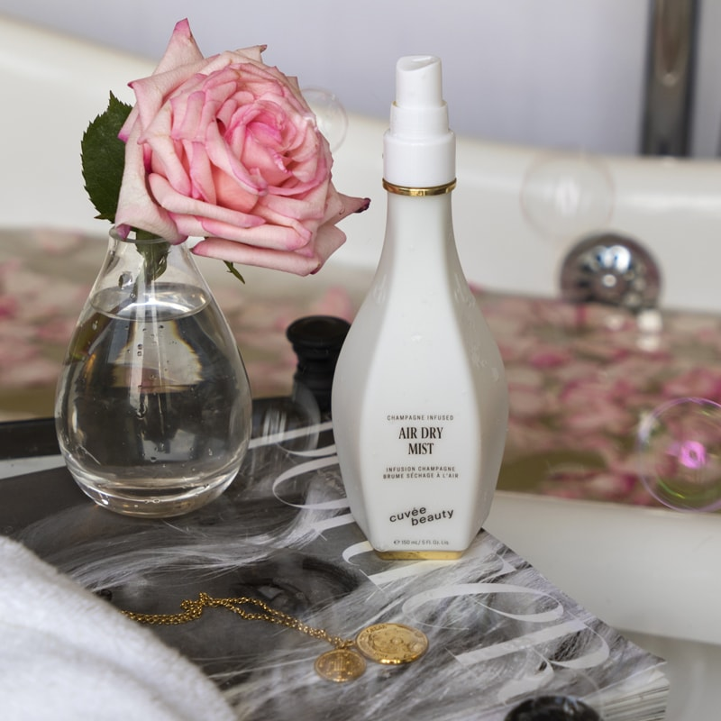 Cuvee Beauty Air Dry Mist lifestyle shot beside a rose