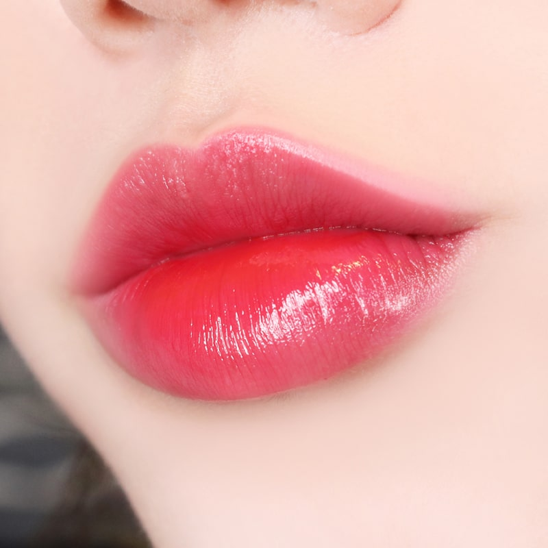 Paul + Joe Liquid Rouge Shine (0.28 oz, Plum Puree (02)) shown on model's lips