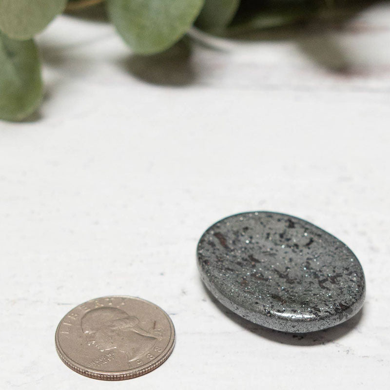 Tiny Rituals Hematite Worry Stone pictured with a quarter to give size perspective (not included)