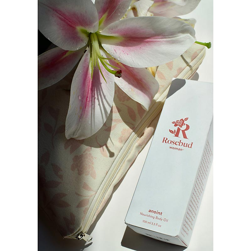 Rosebud Woman Anoint Nourishing Body Oil beauty shot with flower and bag (not included)