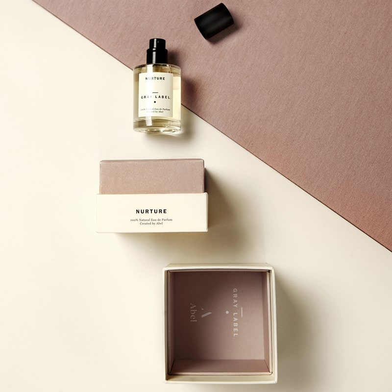 Abel Nurture Eau de Parfum stylized shot showing open box and fragrance on its side with cap off