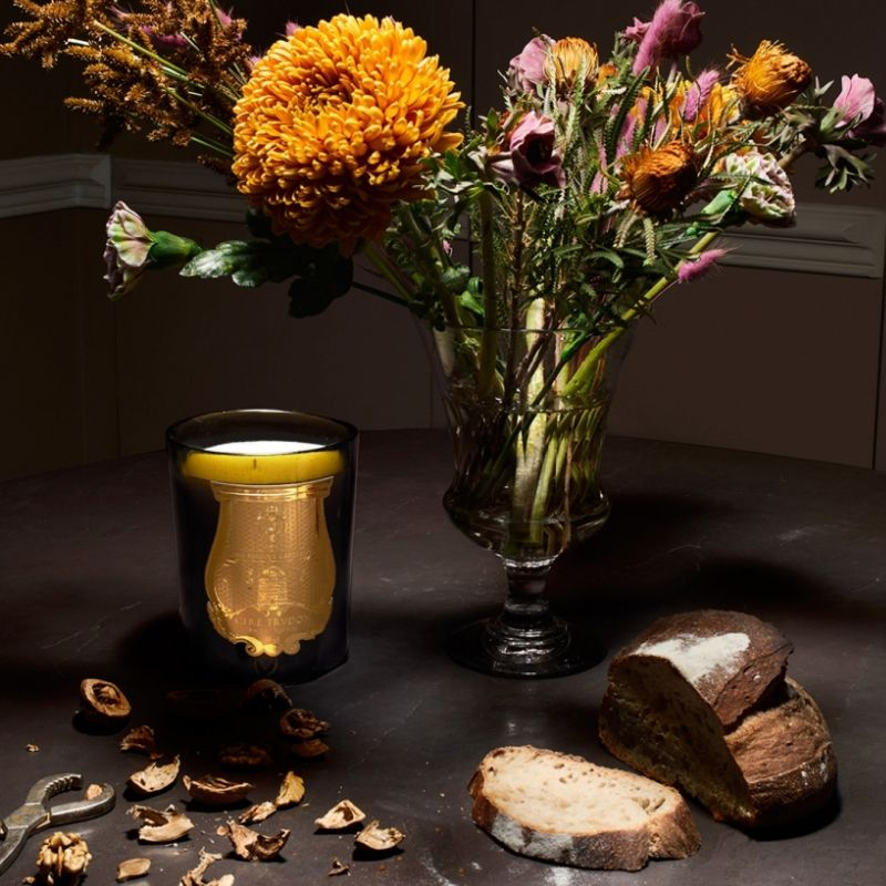 Cire Trudon Cyrnos Candle lifestyle shot with flowers in a vase in the background