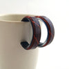Handmade, Eco-Resin Fossil Leaf Black Hoop Earrings, shown with white mug background