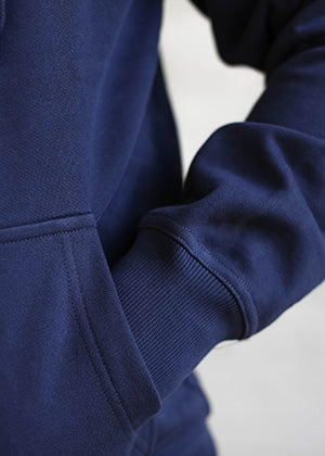 A detailed close up of a pocket on an Ably's men water-resistant hoodie in navy.