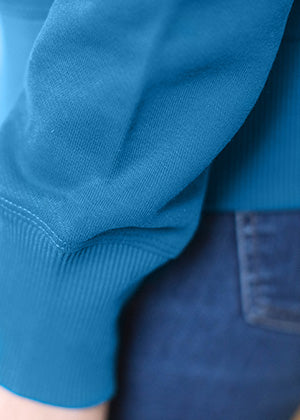 A detailed close up of the sleeve on an Ably's women water-resistant hoodie in Moroccan blue.