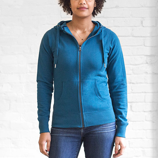 A woman wearing a water-resistant Ably hoodie in Moroccan blue.