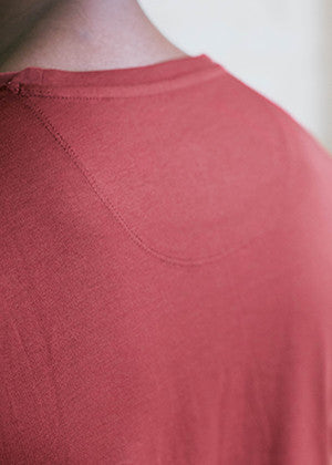 A detailed close up of the collar on an Ably's men water-resistant pocket tee in maroon.