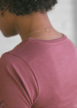 A detailed close up of the collar on an Ably's women water-resistant pocket tee in plum.