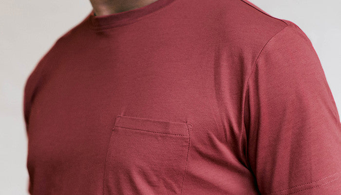A detailed close up of the chest pocket on an Ably's men water-resistant pocket tee in maroon.