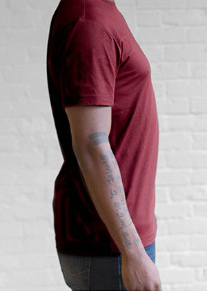 A detailed close up of the side on an Ably's men water-resistant pocket tee in maroon.