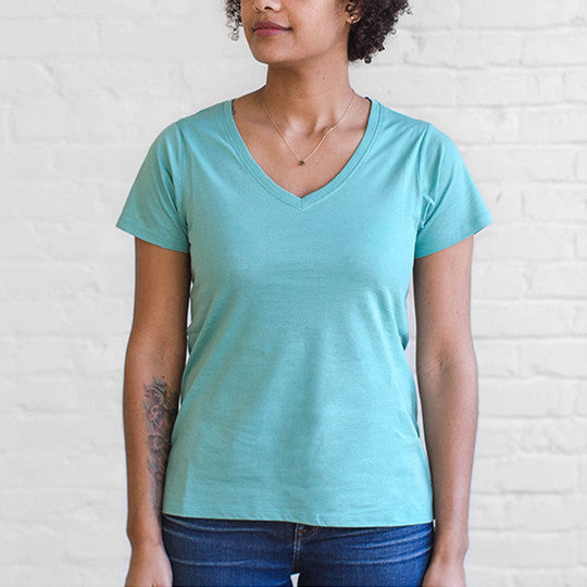 A woman wearing a water-resistant Ably v-neck tee in Canton blue.