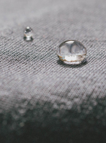 A close-up of a water droplet on Heather gray Ably water-resistant apparel.