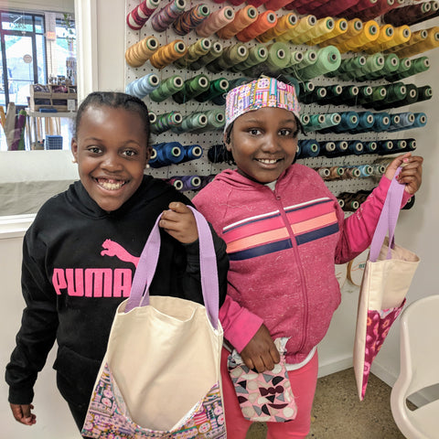 two children holding handmade tote bags proud in a classroom