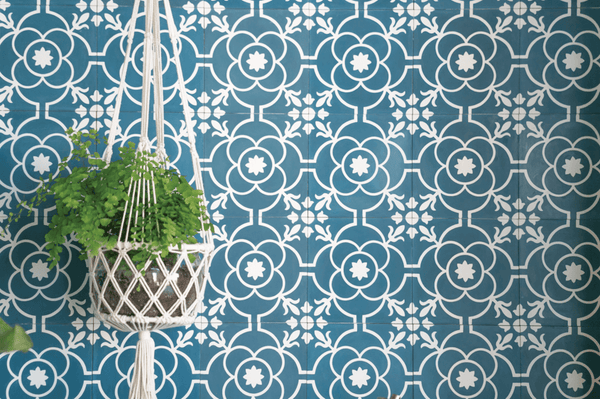 A hanging fern against a background of blue and white Exfloorit fleur-de-lis wall tiles.