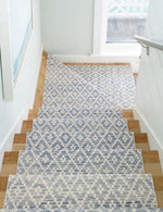 Stairs with a blue cotton runner with a diamond pattern