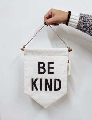 Hand holding be kind banner