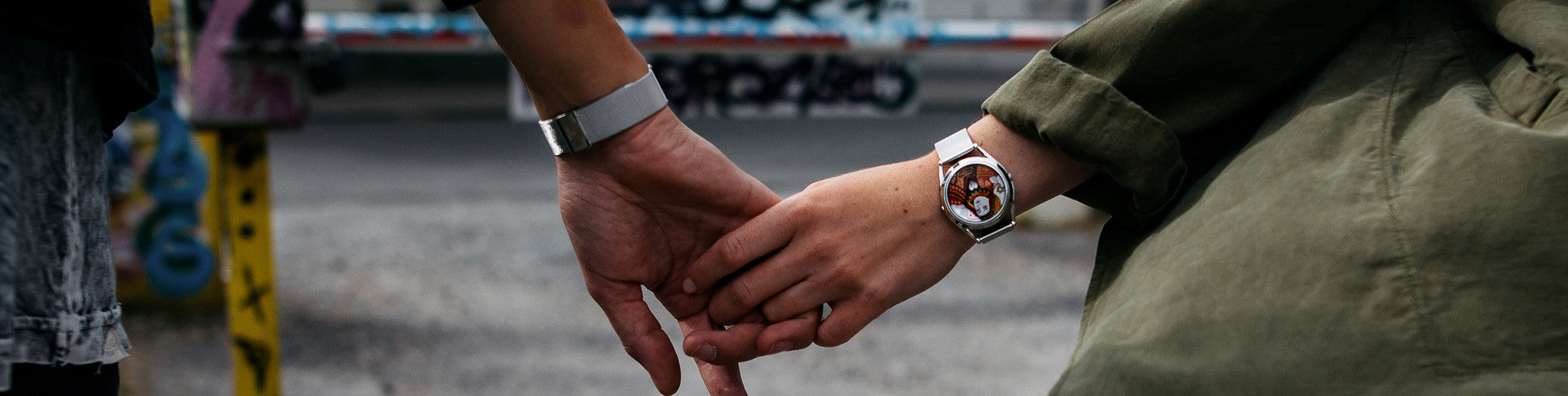 couple holding hands with King and Queen watches