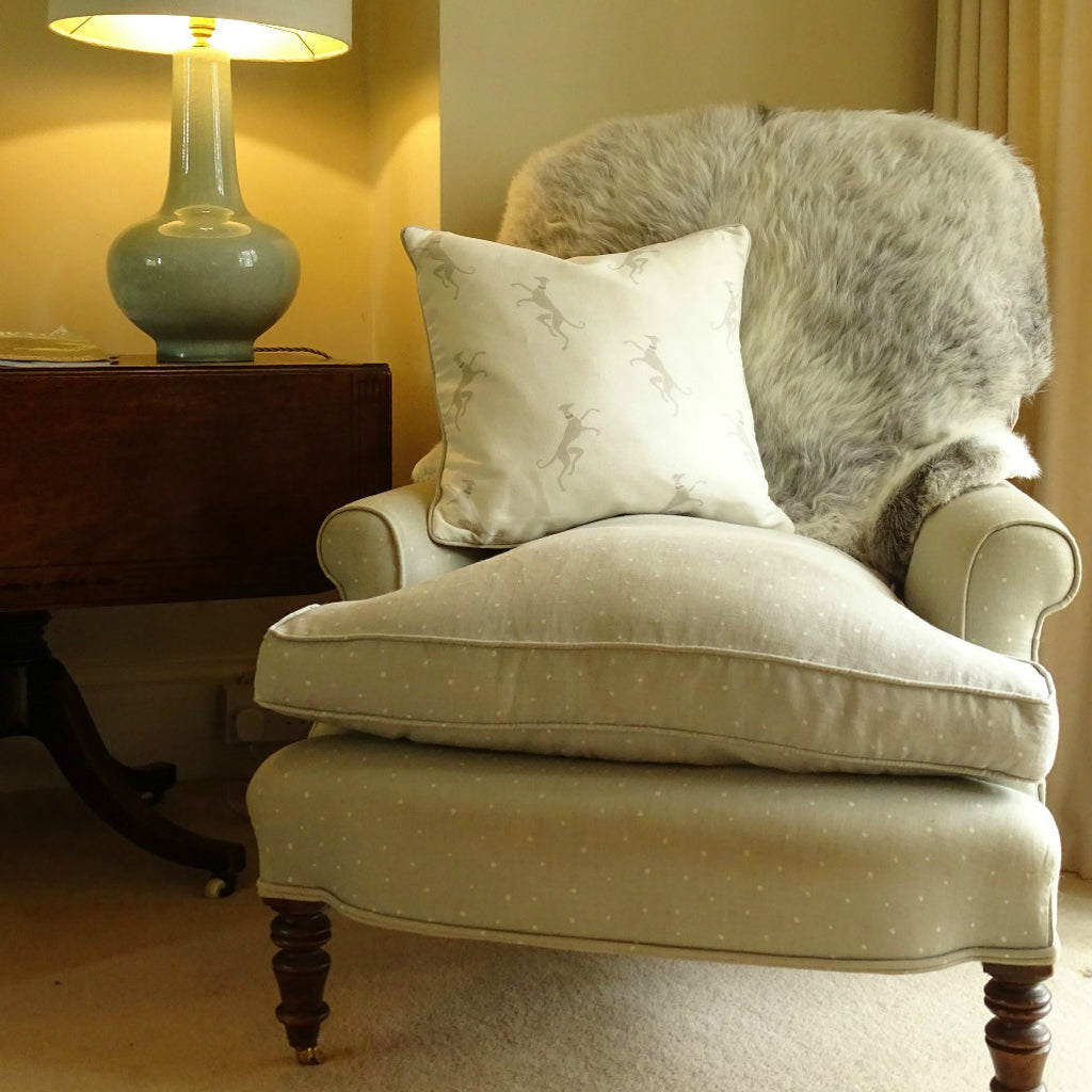 Herdwick sheepskin draped over back of a chair with rearing whippet cushion