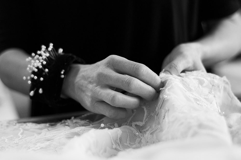 Couturier pinning french lace for wedding dress