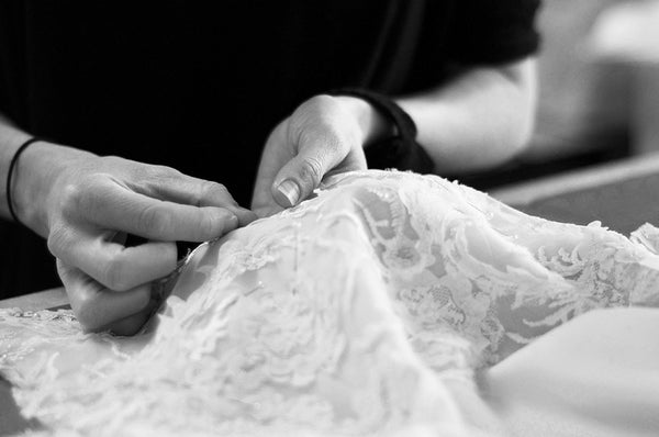 Couturier pinning french lace wedding dress