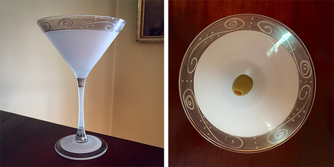 The Statesman martini glass shot indoors in a dining room from the side and from above.