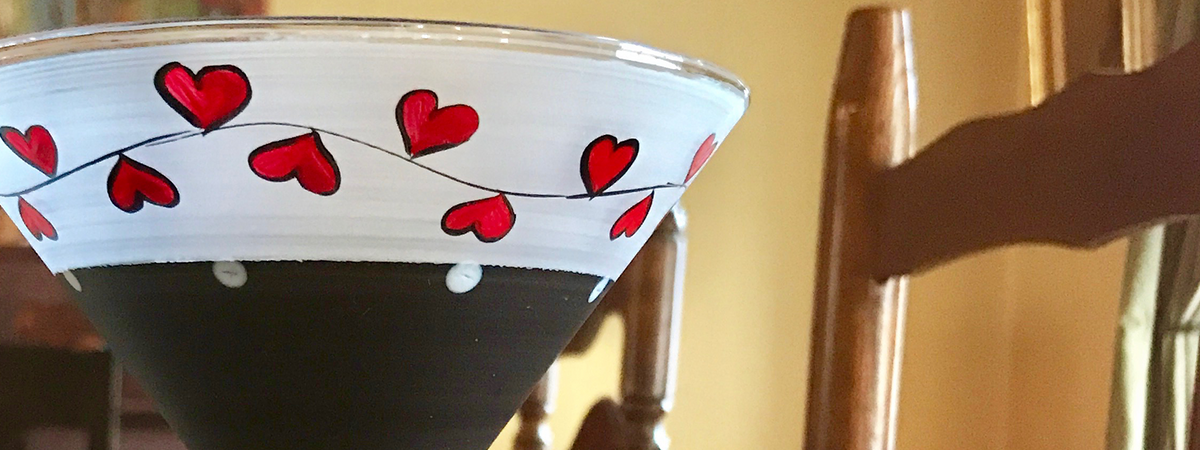 Valentini martini glass shot in a dining room table with red hand-painted hearts and black bowl. Perfect for Valentine's Day.