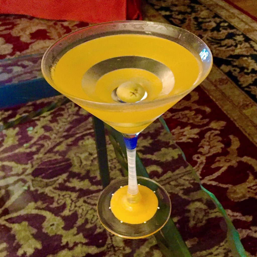 Suntini martini glass at Tini Grails has yellow stripes and base and a blue and white stem, shot in a living room.